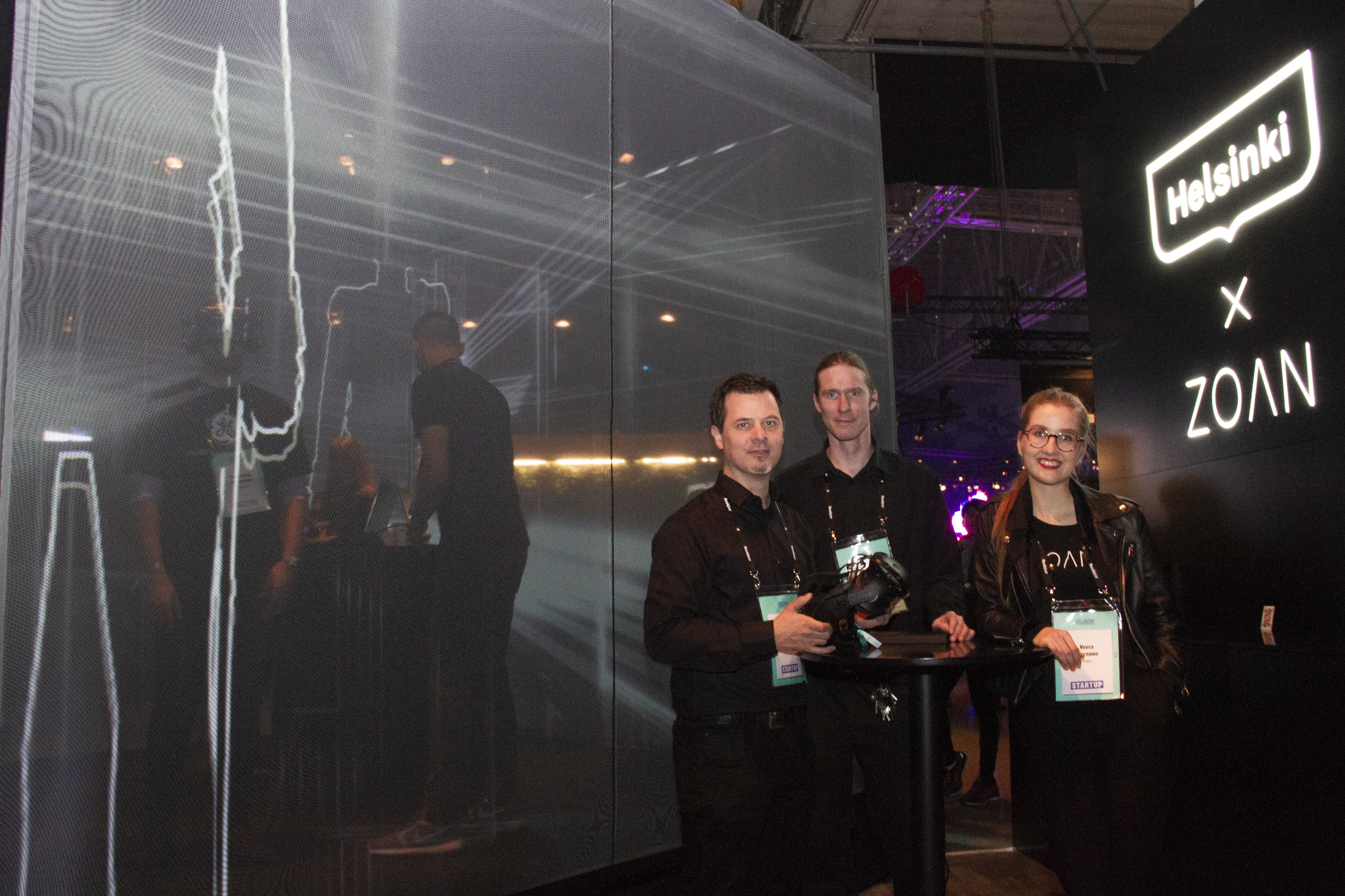 """The Zoan team, represented by its office manager Veera Varnamo (right), Janne Itäpiiri (left) and the designer Aki Hirvilammi (middle), demonstrated a virtual reality cube that gave Slush visitors an opportunity to travel to multiple places all over the Finnish capital area, such as Senate Square, the home of Alvar Aalto and Lonna island. """"What I like about the virtual reality is how easy it puts smiles on people´s faces once they put on the glasses,"""" Veera said."""