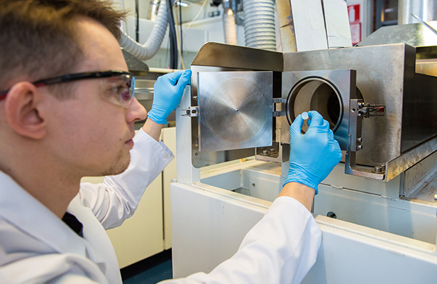 Doctoral canditate Mikko Nisula holds in his hand a sample on a steel substrate.