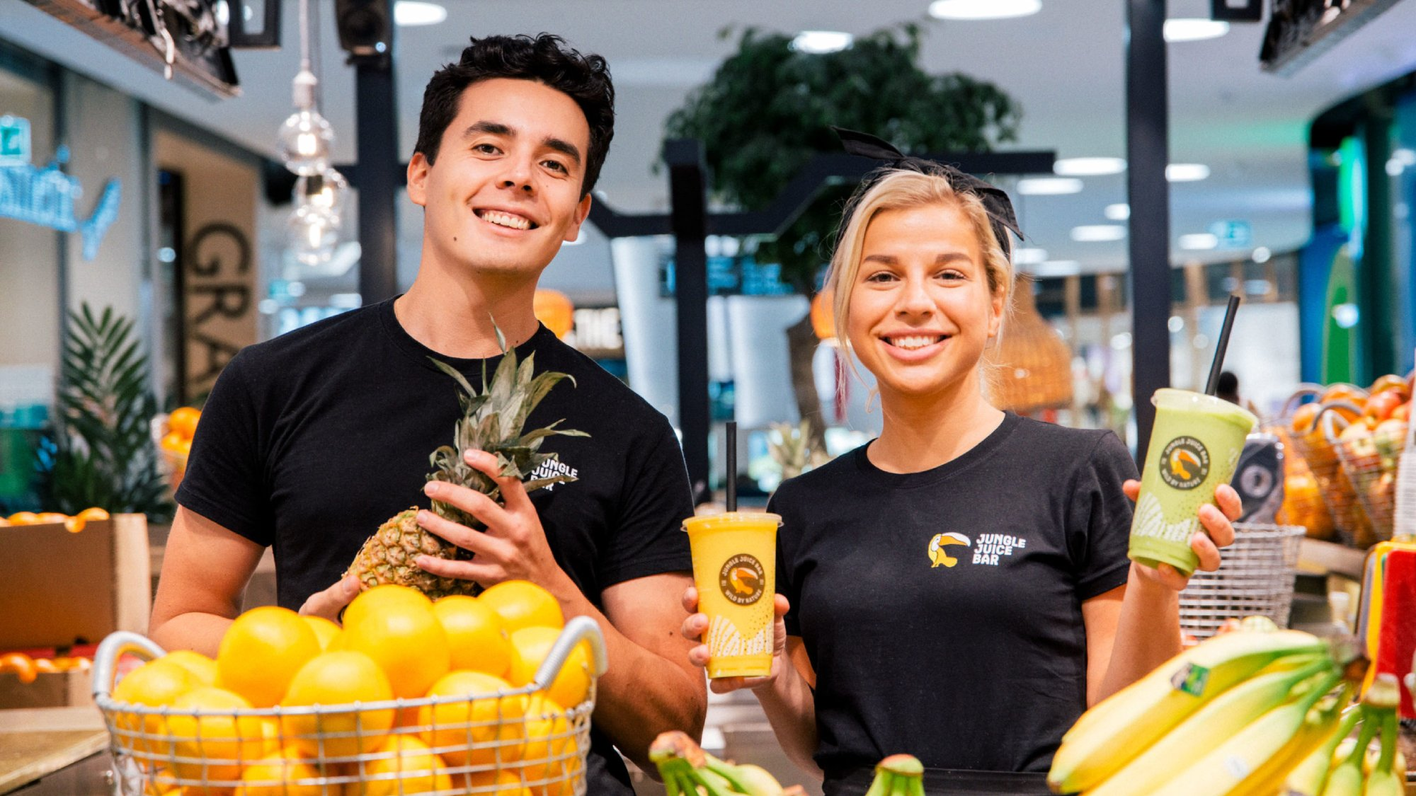 Juice makers smiling behind a fruit table