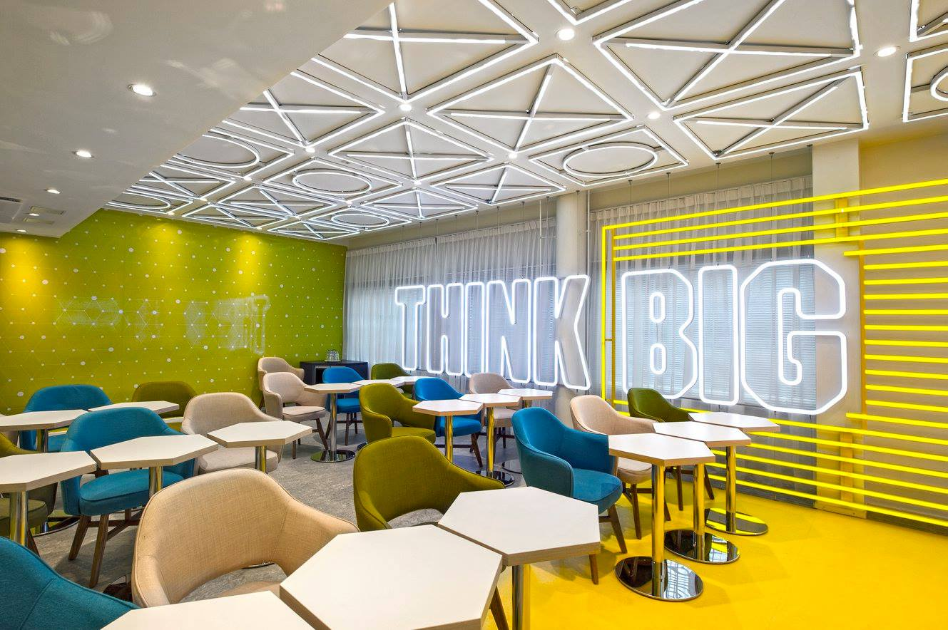yellow-designed meeting room with huge Think Big sign