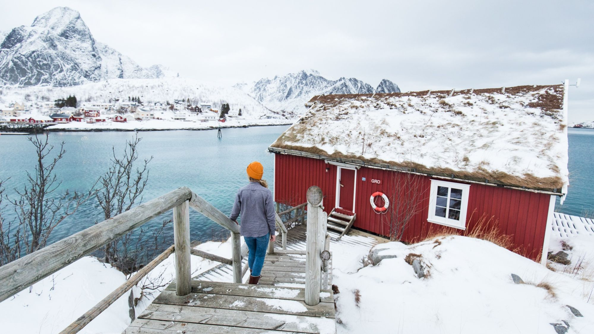 Woman walking to a cottage nearby a frozen sea