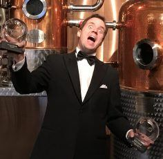 The ecstatic CEO of Hernö Gin holds up two International Wine & Spirit Competition awards.