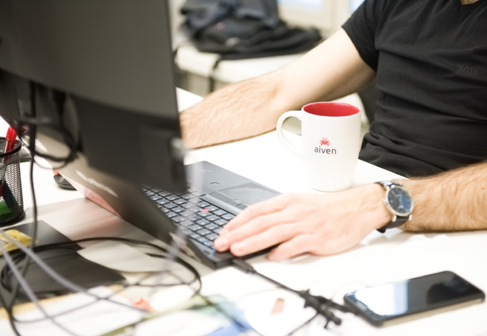 Man sitting by computer with an Aiven mug
