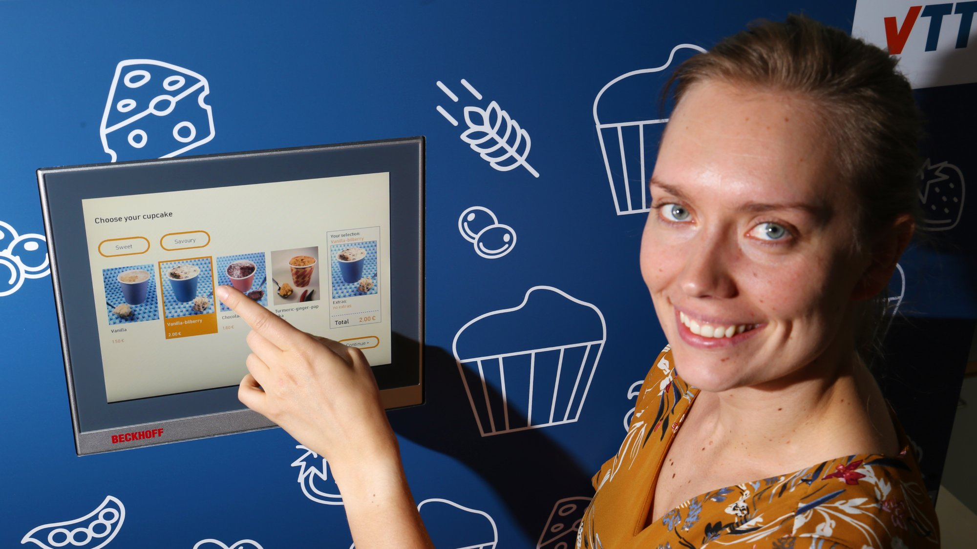 woman pointing a vending machine's touchscreen