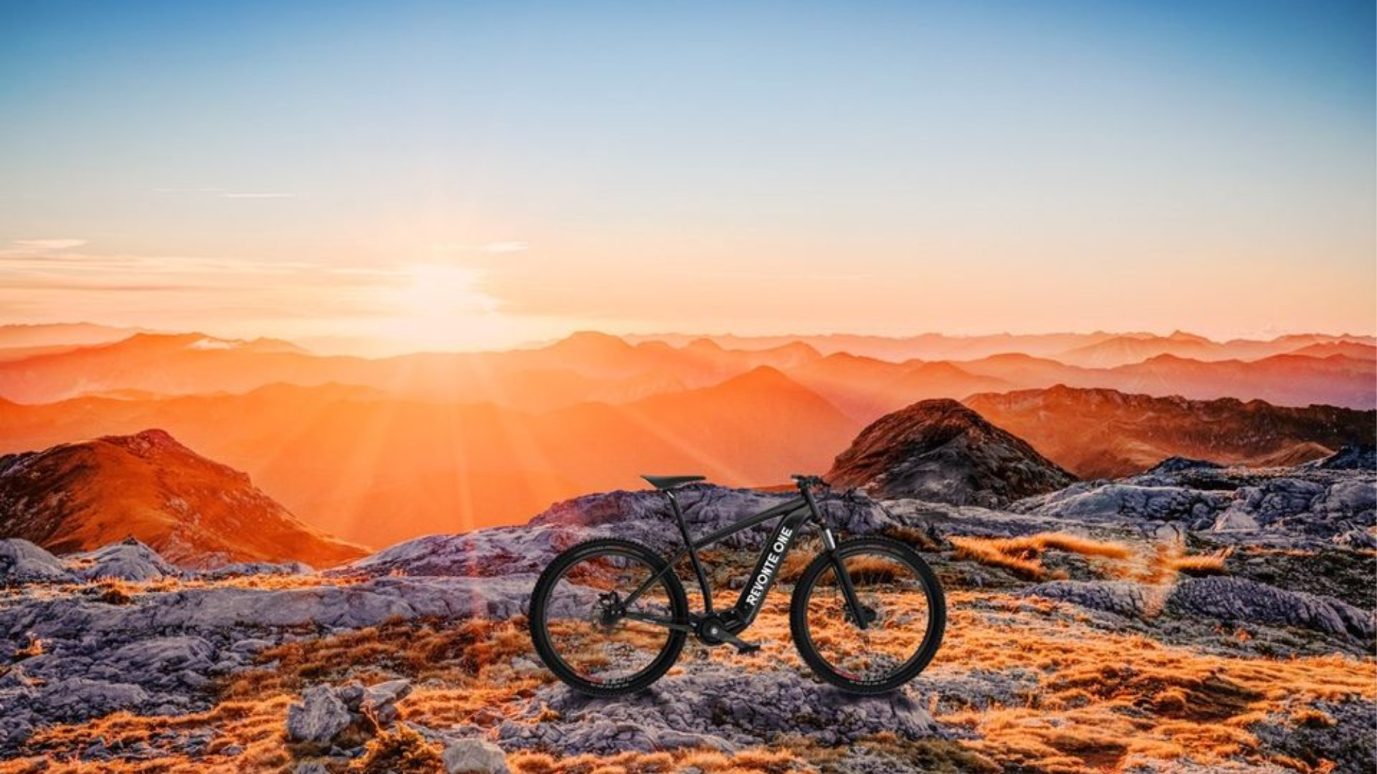 A Revonte bicycle on a mountain at sunset