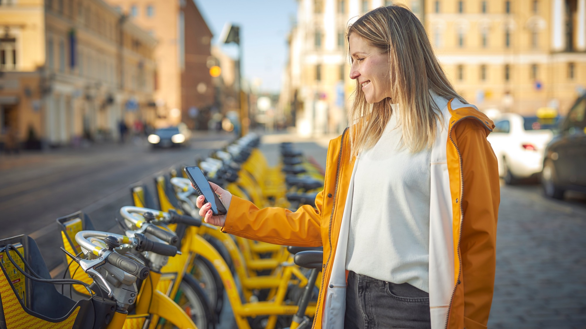 A woman unlocking a city bike with her phone