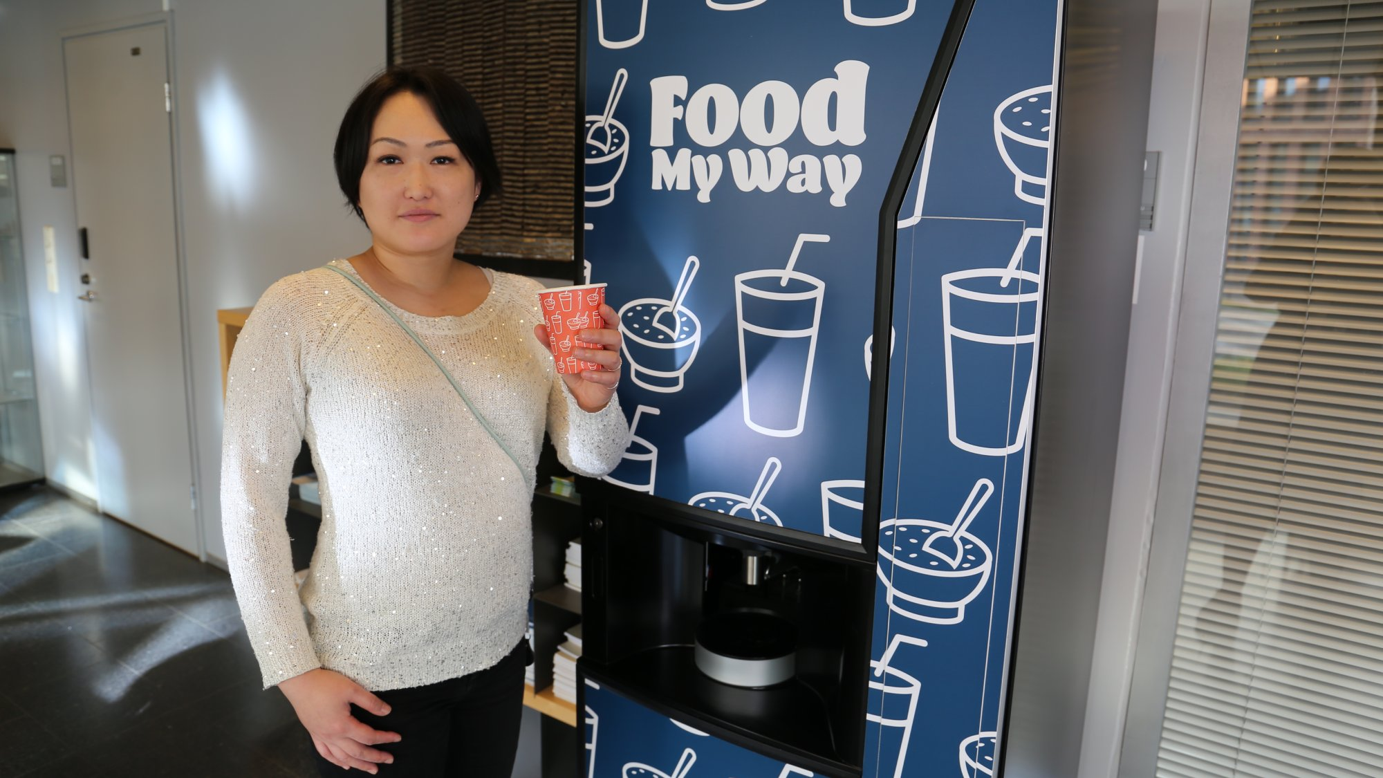 a woman holding a cup in a front of a snack machine