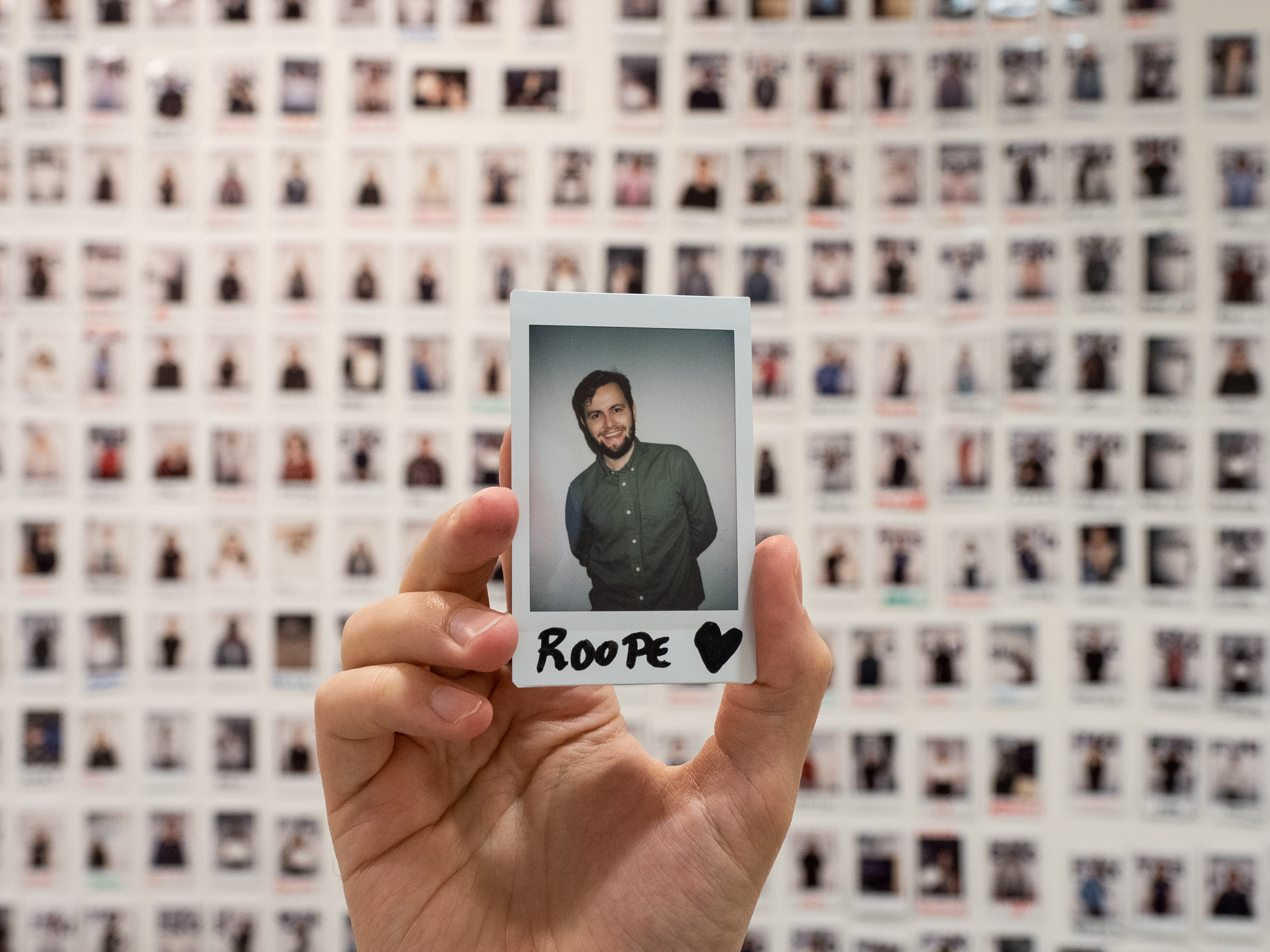 Country manager Roope in front of cleaner polaroid wall.