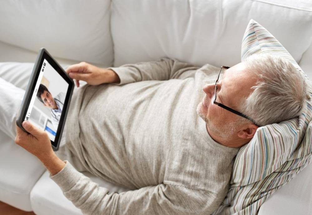 Man lying on couch using tablet