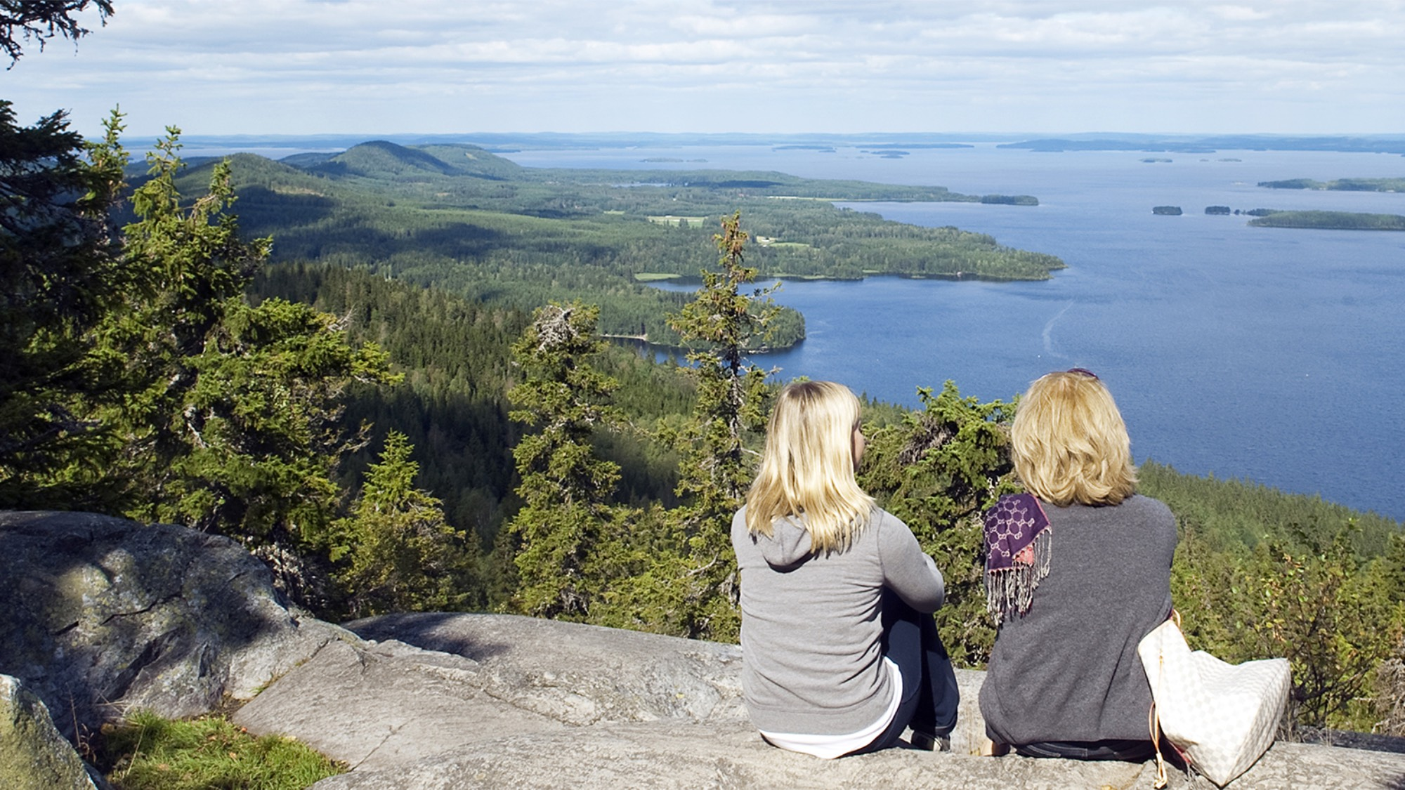 Two women sitting on a cliff overlooking a big lake