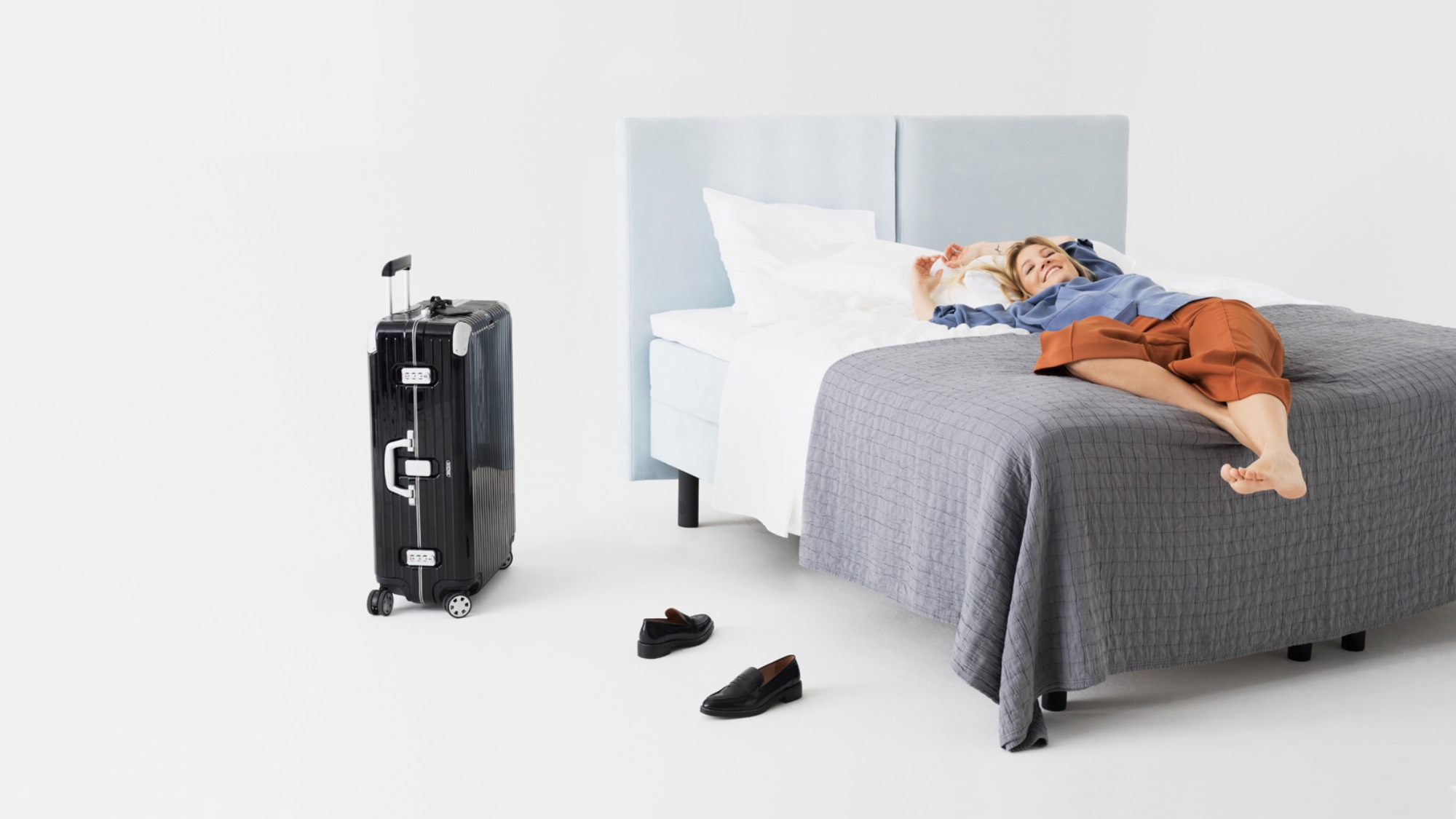 Woman lying on a bed with suitcase on the floor
