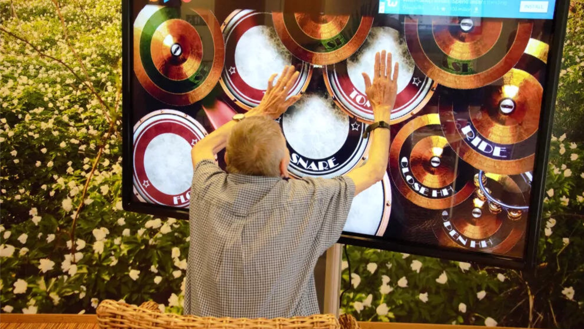 An old man tapping on drums displayed on a massive screen