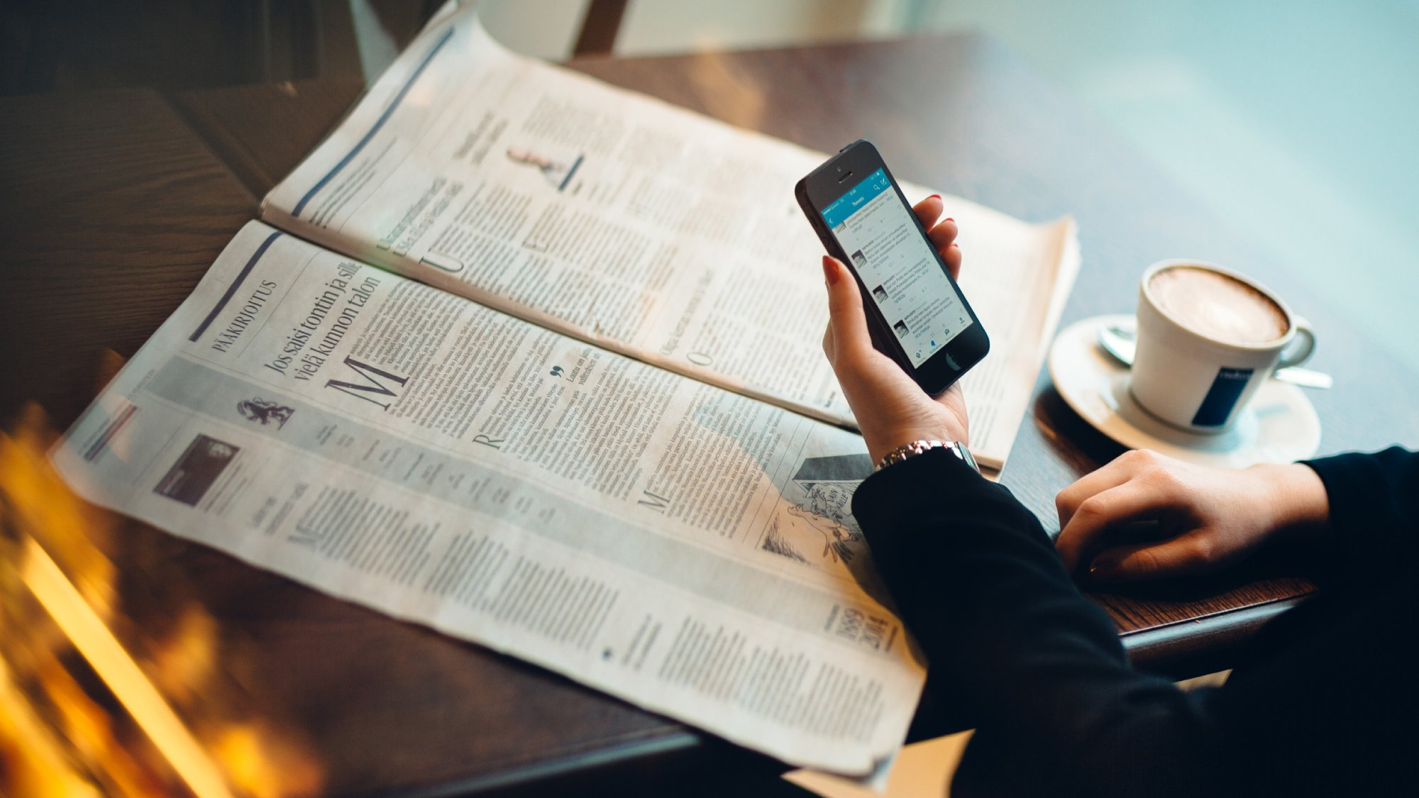 Woman holding a mobile phone while reading a newspaper