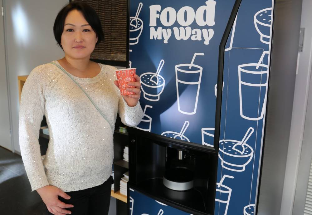 woman standing in front of food vending machine