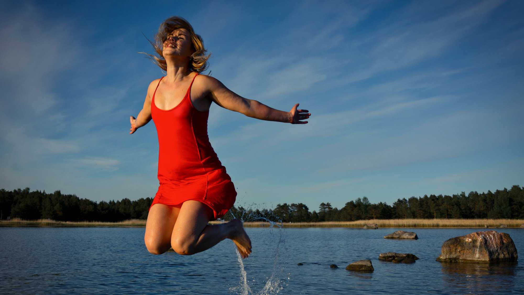 woman jumping in the air next to lake