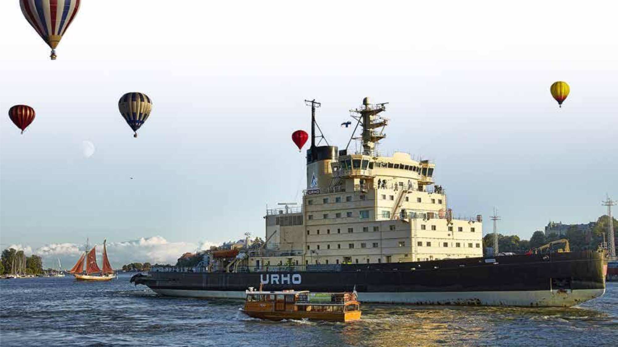 A large icebreaker surrounded by hot air balloons