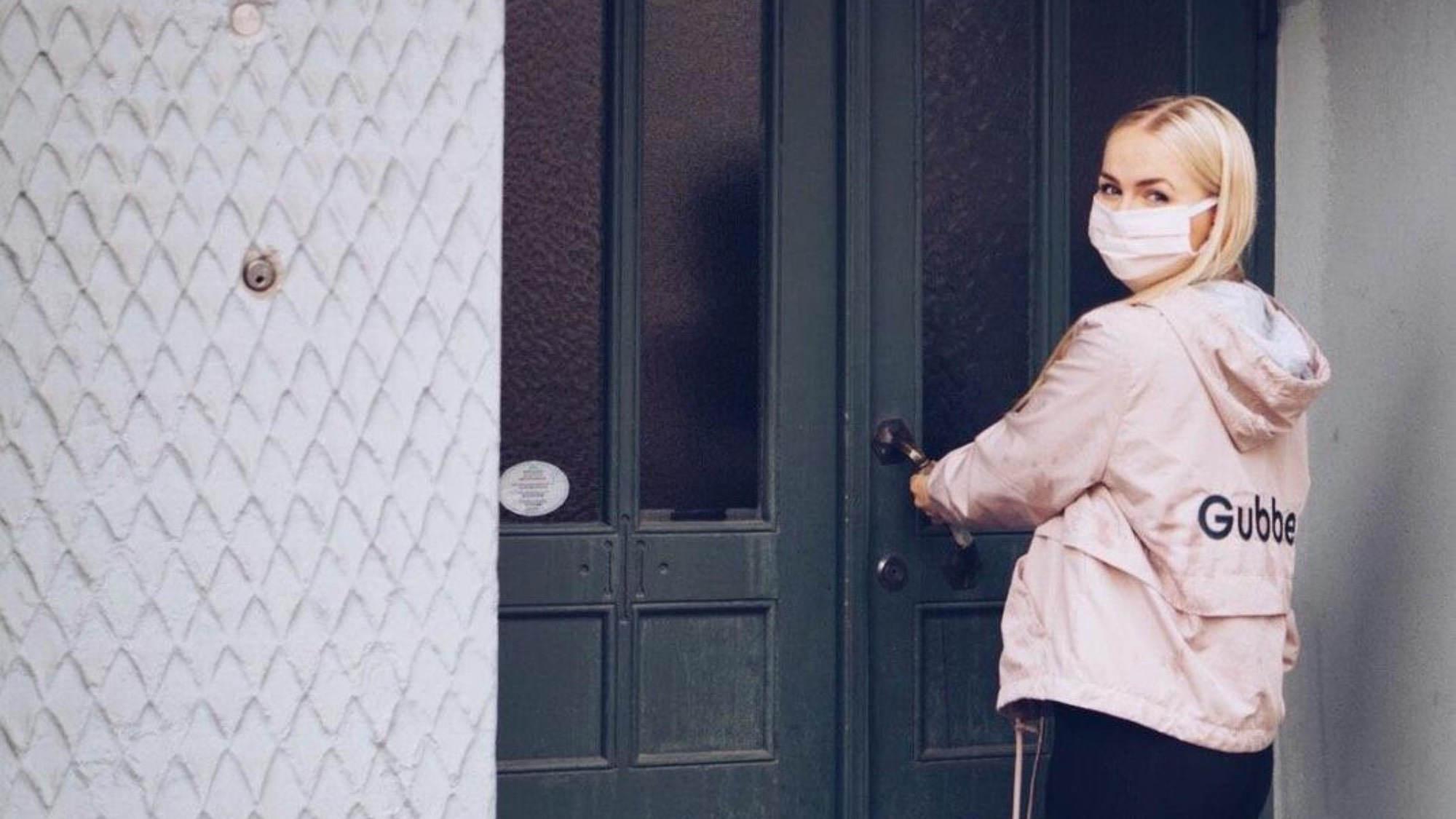 A young woman by a door wearing a pink face covering