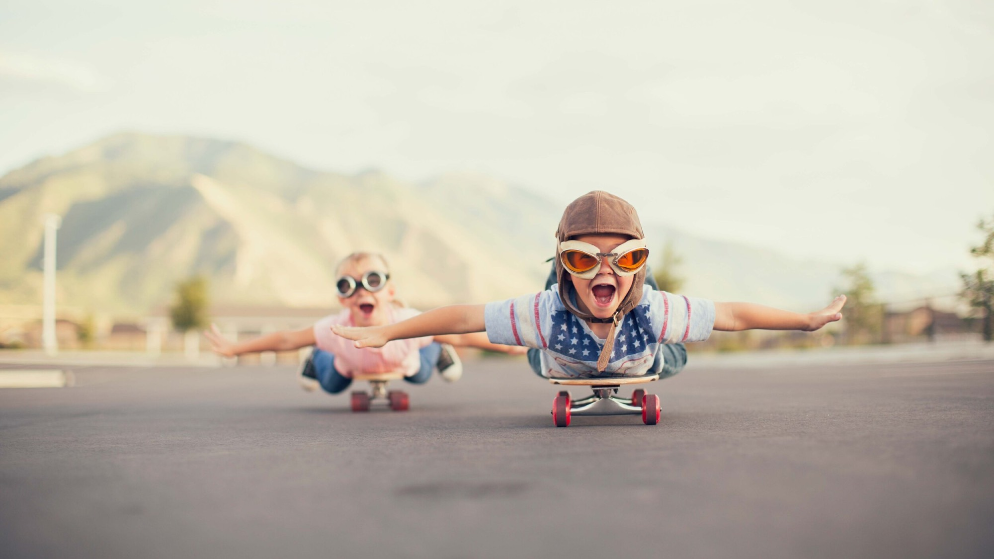 Two kids lying on skateboards and rolling down the street