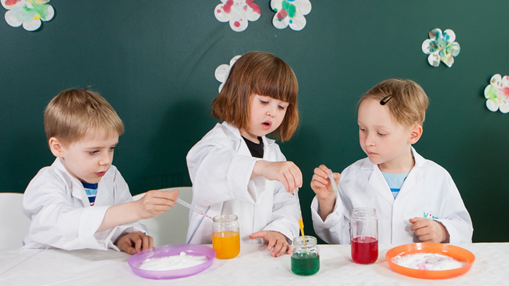 Three kids dressed as scientists carry out an experiment