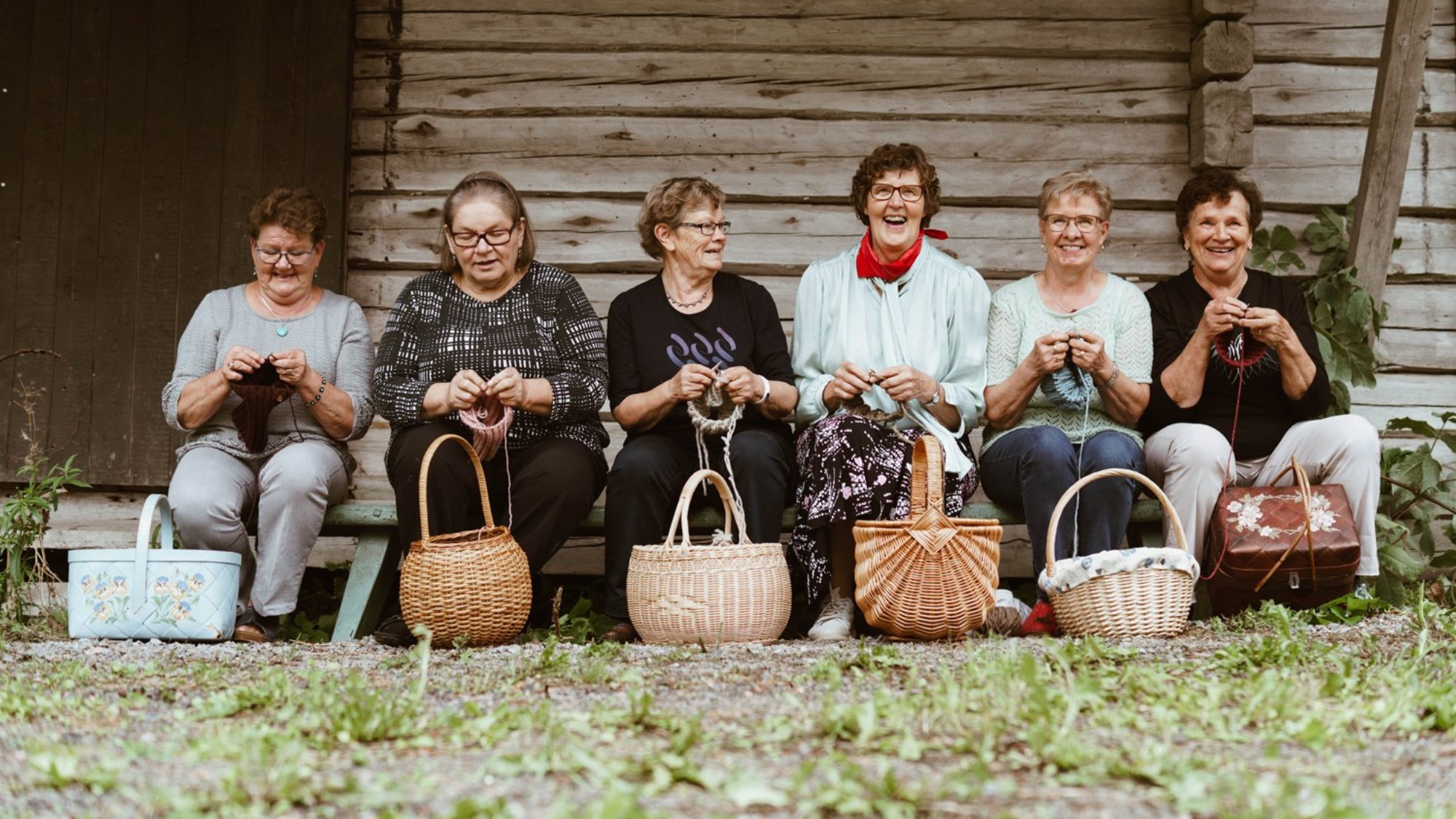 Myssyfarmi grannies smiling and knitting in front of a timber house