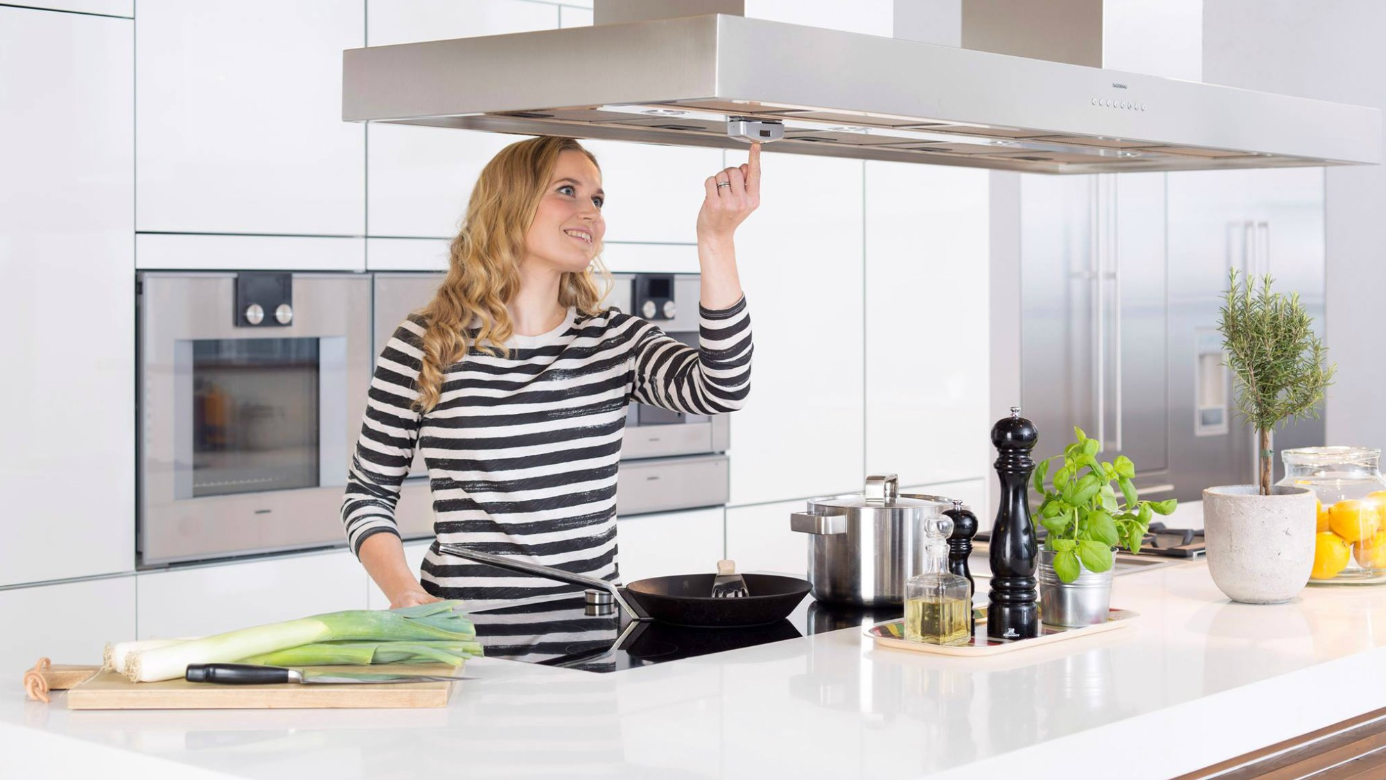 Woman pressing on a device above a stove