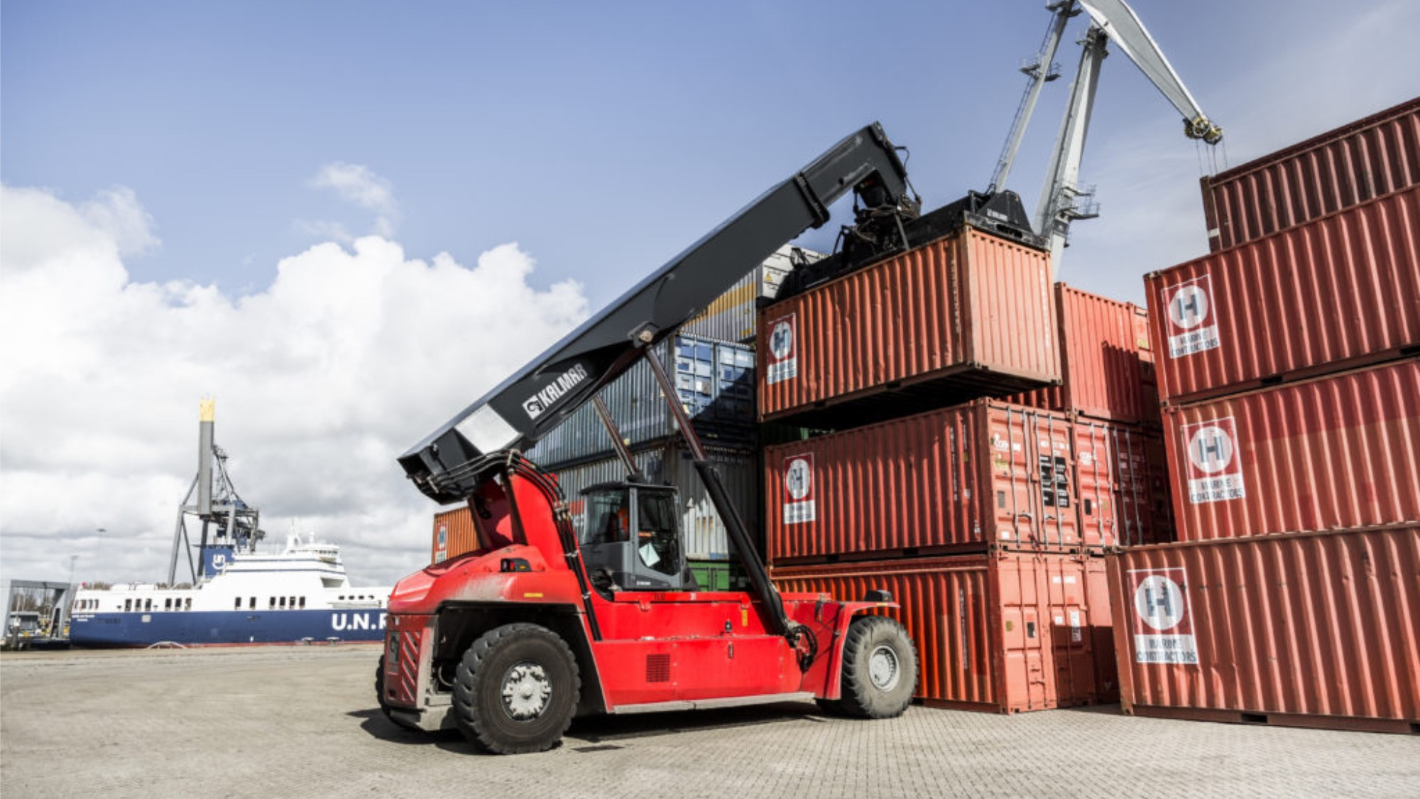 A red reachstacker lifting a container