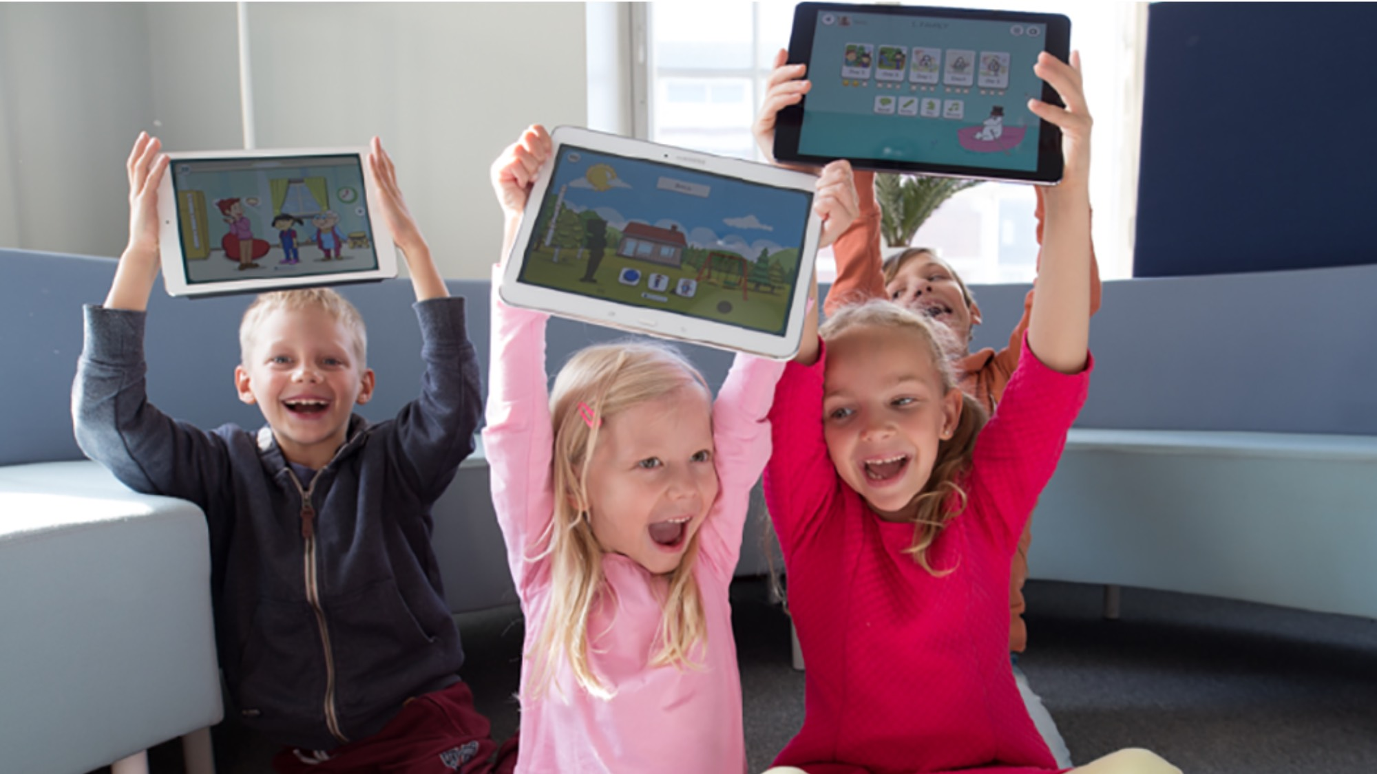 Kids holding up tablets with games on the screens