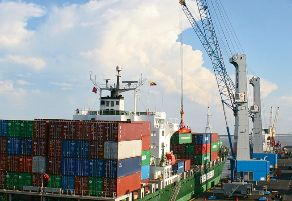 A crane lifting containers off a cargo vessel