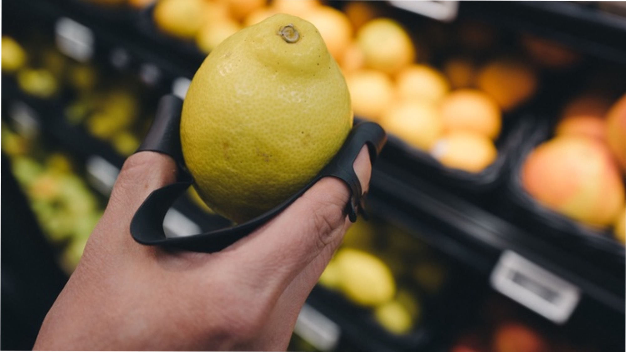 The Koura protective glovel holding a lemon in a shop