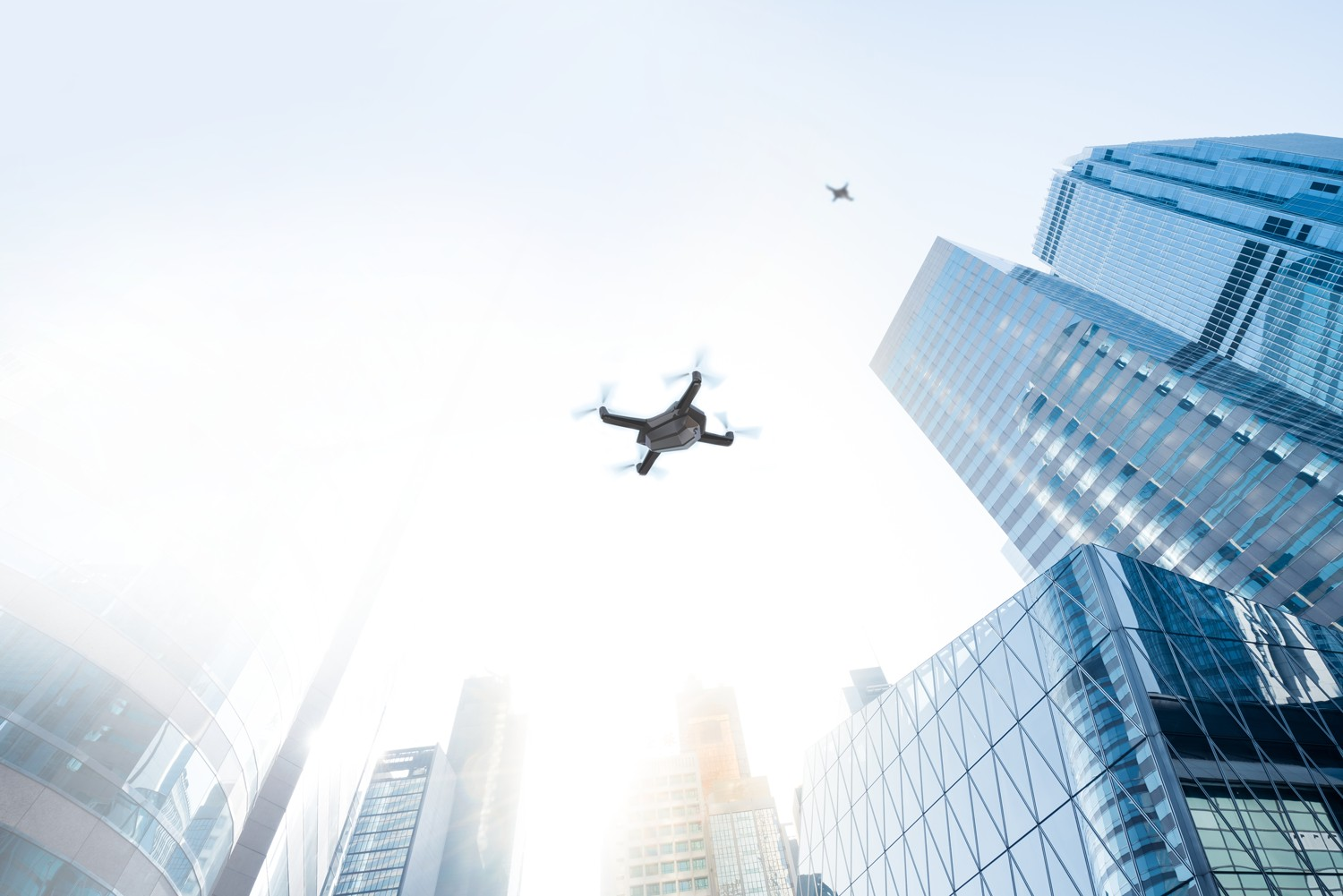 A drone flying next to skyscrapers