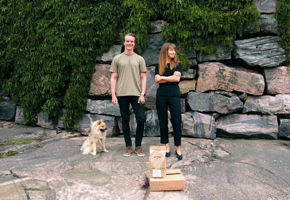 man and woman stand with a dog