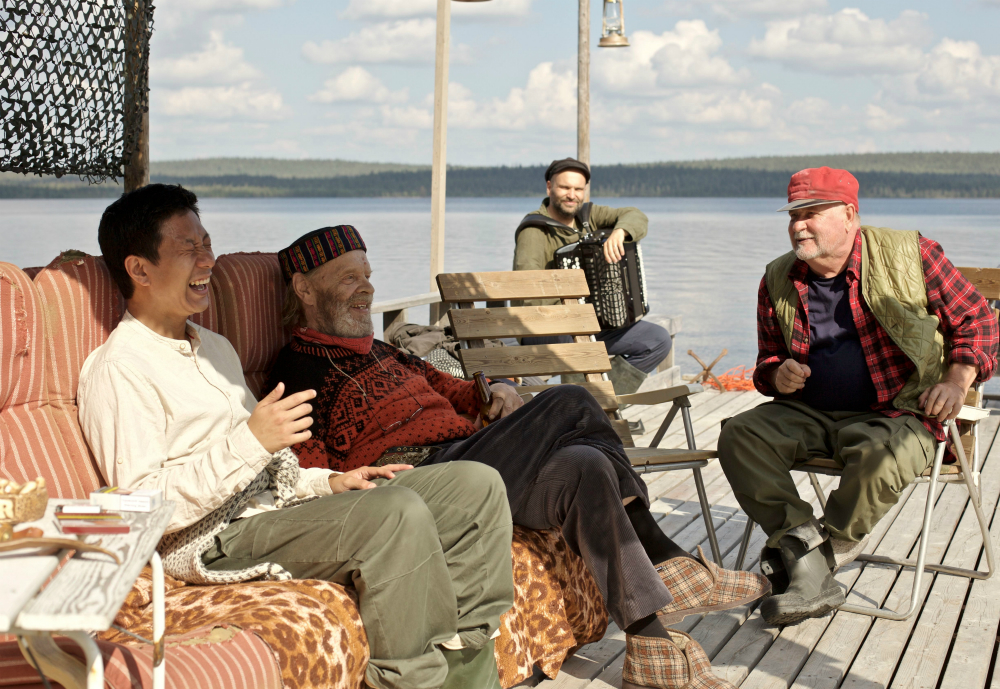 Cheng laughs with three local men by a lake