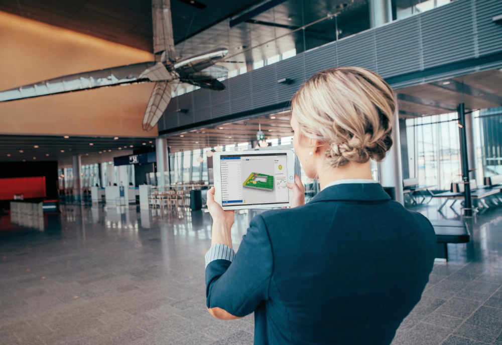 Woman holding up a tablet at a airport.