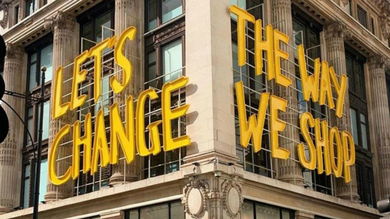 A sign saying Let's Change The Way We Shop.