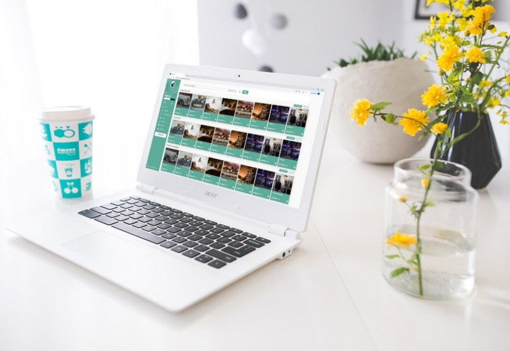Opened laptop next to flowers and coffee cup