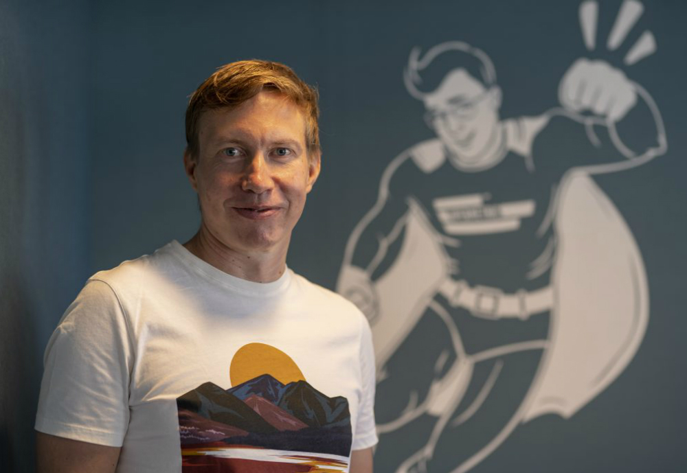 Supermetrics CEO in front of humorous superhero wallpainting.