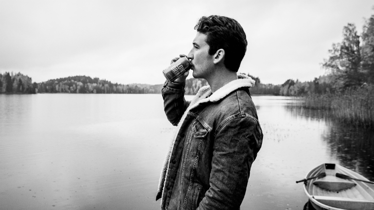Miles Teller drinking long drink by water.