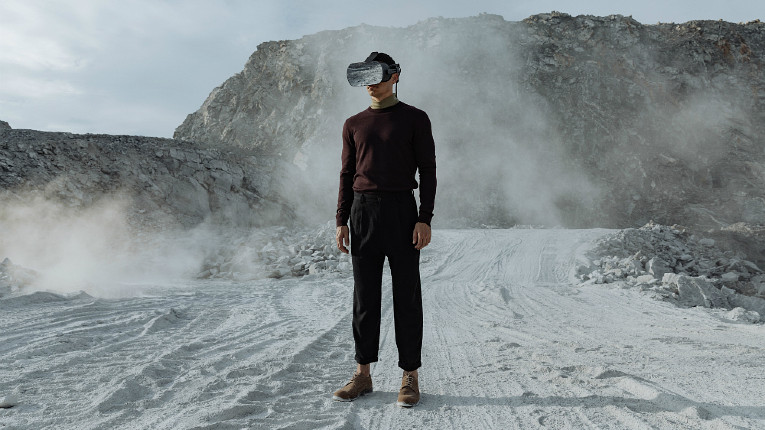 Man wearing VR headset standing in dusty and rocky terrain