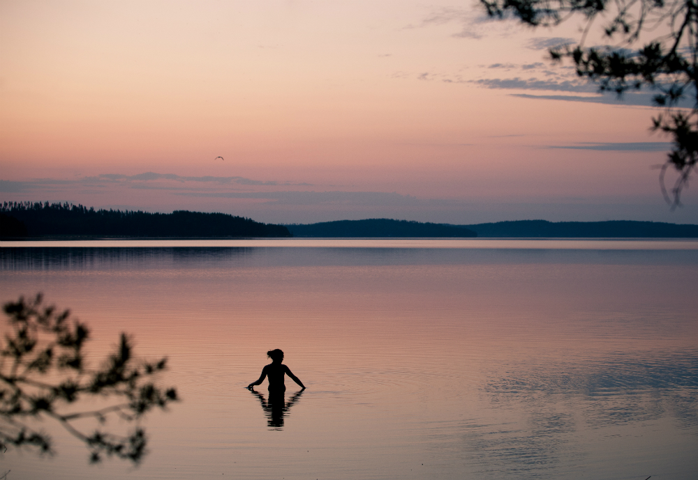A lone swimmer in colourful Finnish summer night
