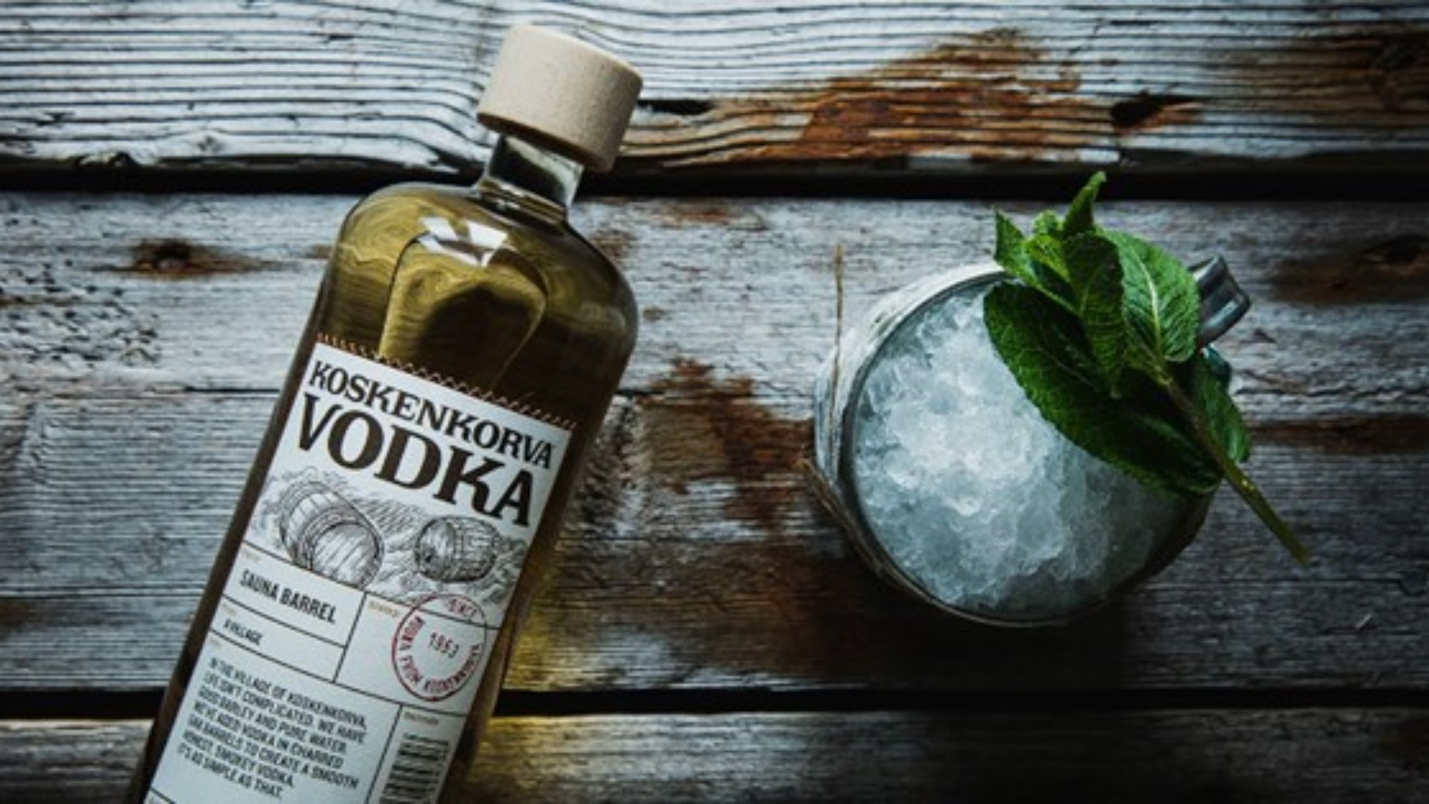 A bottle of Koskenkorva vodka next to a glass with a drink