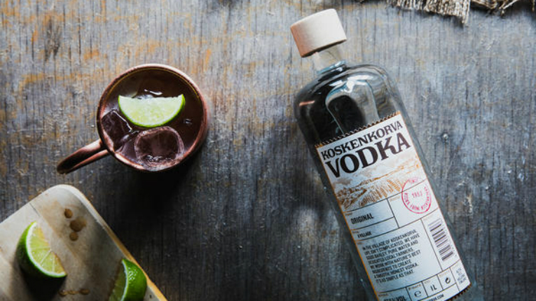 A bottle of Koskenkorva vodka next to a cup and chopped up lime.