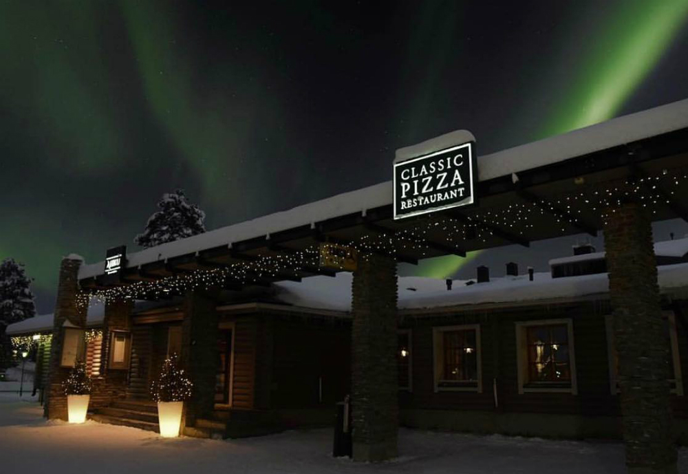Northern lights shining over a Classic Pizza restaurant.