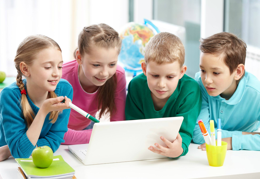 Four children looking and pointing at laptop.