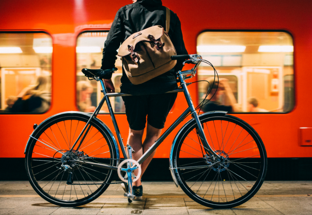 Cyclist leaning on bike in front of metro.