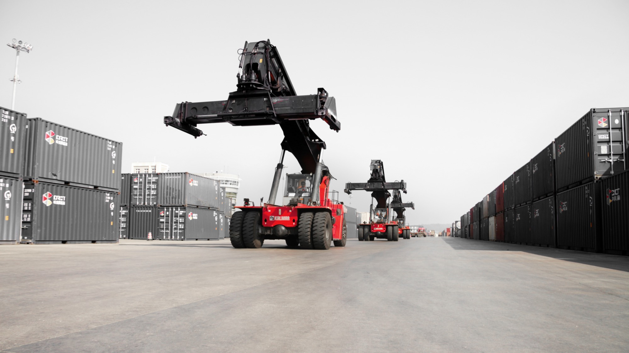 Kalmar reachstackers surrounded by containers.