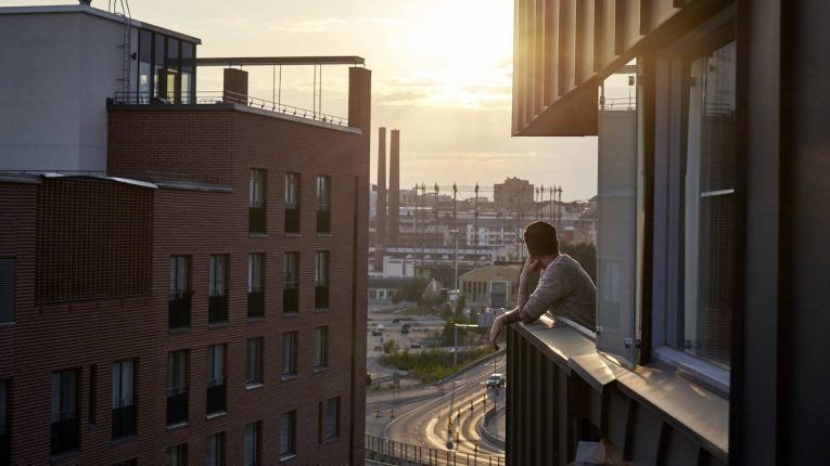 man looking at sunset from his balcony