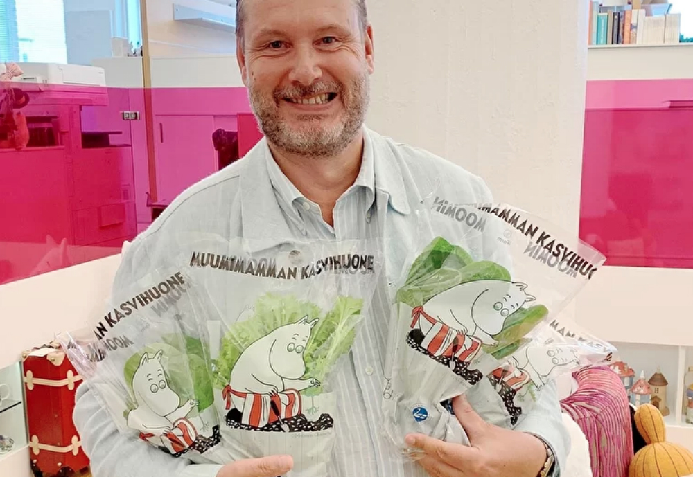 Man holding salad packaging with images of Moominmamma.