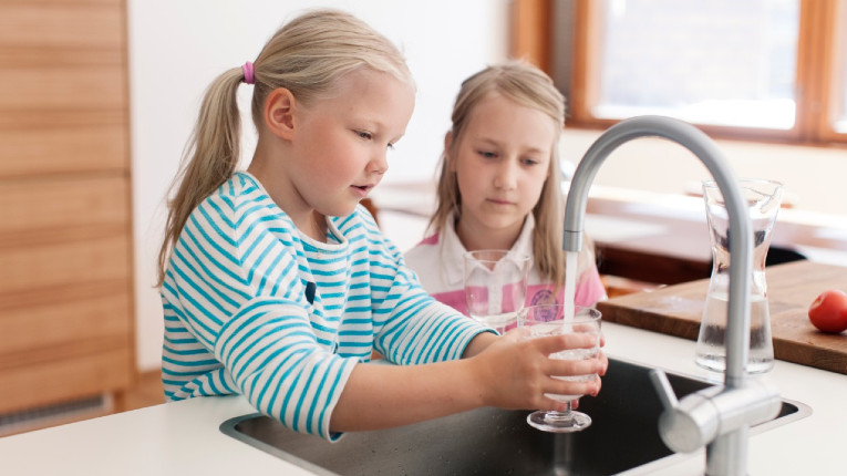 Two girls filling a cup with tap water.