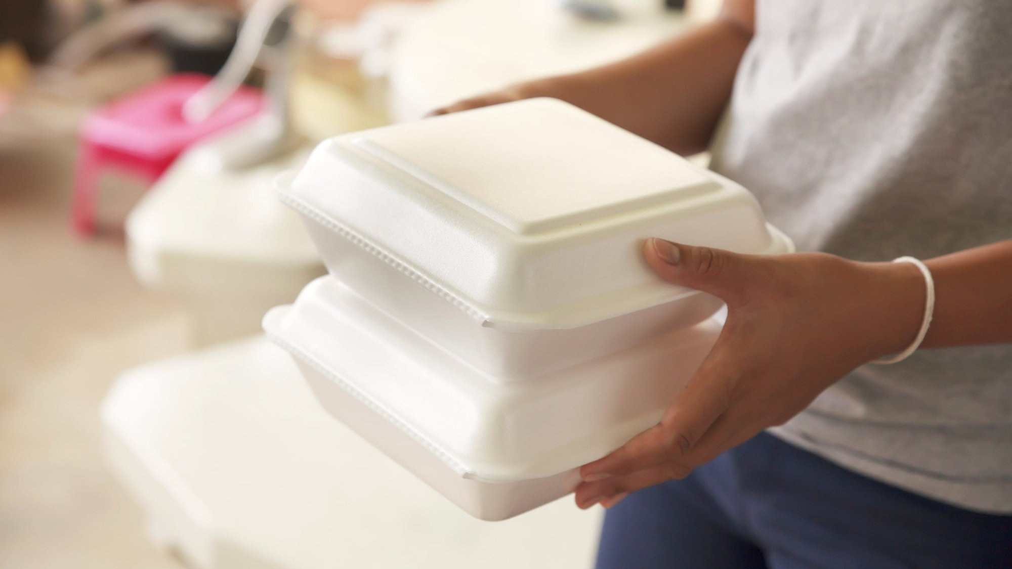 A person holding two polystyrene foam containers.