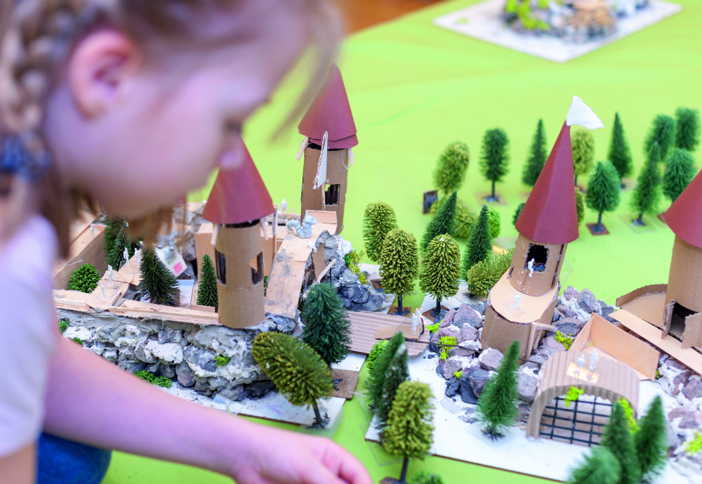 Girl adjusting something on a miniature model of a town